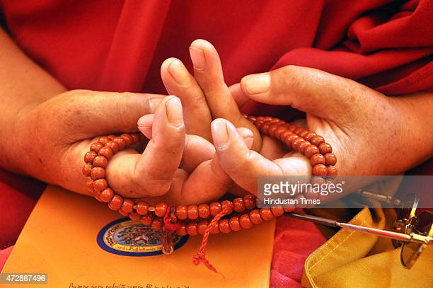 Buddhist monk holds a rosary in a distinct fashion during a prayer session at Gyuto Tantric Monastery as Tibetan spiritual leader Dalai Lama arrives...