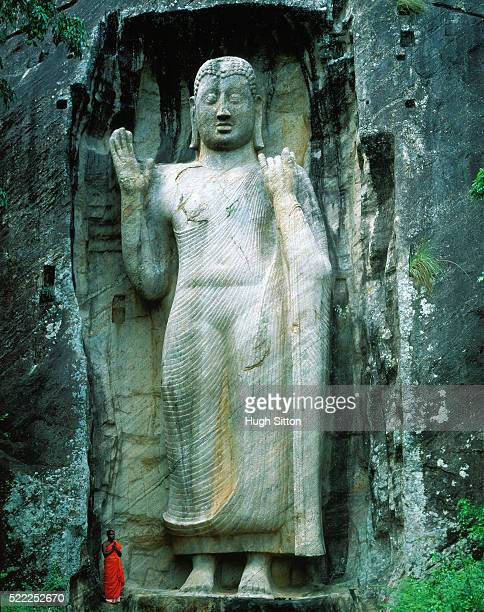 buddhist monk in front of statue, sri lanka - hugh sitton stock pictures, royalty-free photos & images