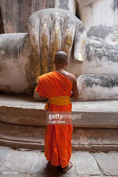 buddhist monk in front of the seated buddha at wat si chum, sukothai, thailand - hugh sitton stockfoto's en -beelden