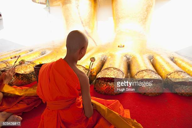 buddhist monk in front of the standing buddha, wat indravihan, bangkok, thailand - hugh sitton stock pictures, royalty-free photos & images