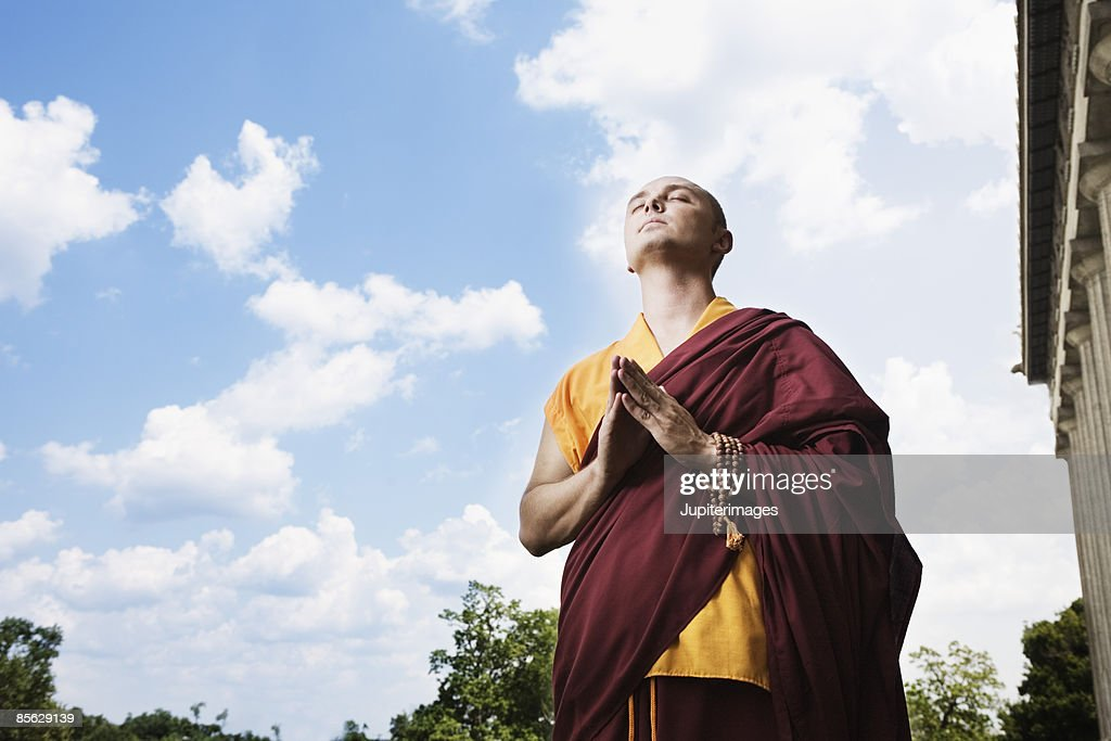 Buddhist monk in prayer pose : Stock Photo