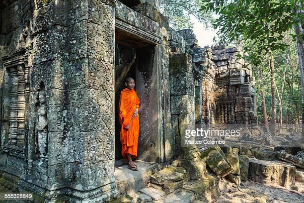 Buddhist monk inside Angkor wat old ruin, Cambodia