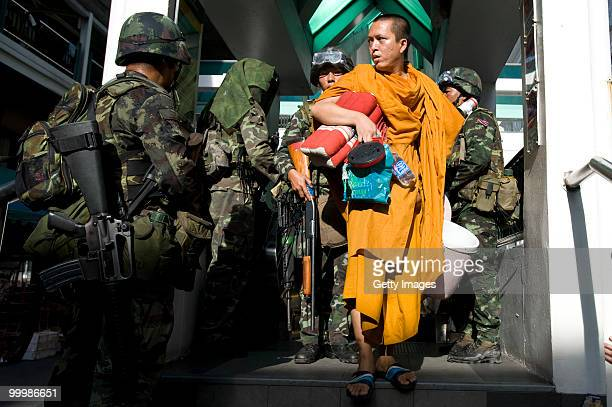 Buddhist monk is greeted by Thai soldiers as he descends from an elevated train platform on May 19 2010 in Bangkok Thailand At least 5 people are...