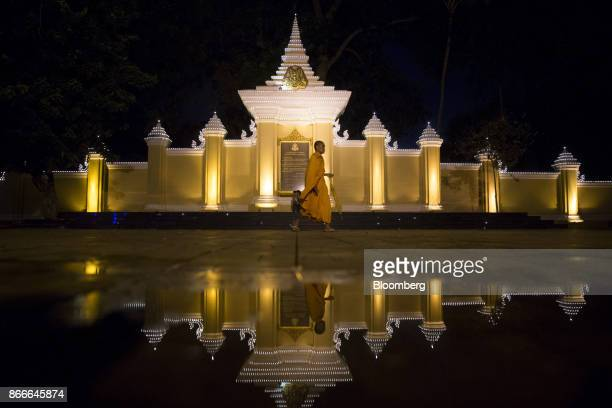 A Buddhist monk is reflected in a puddle as he walks past an illuminated wall of the Royal Palace in Phnom Penh Cambodia on Monday Oct 23 2017 The...