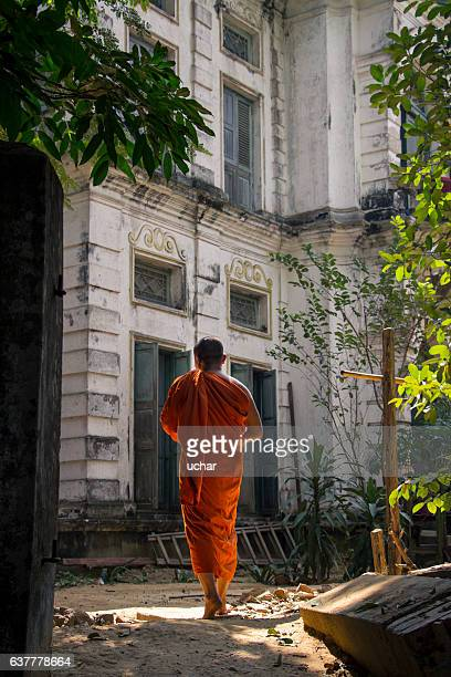 Buddhist monk is walking in front of an old building