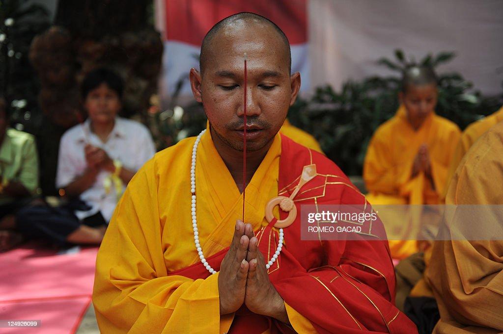 A Buddhist monk leads prayers at the lau : News Photo