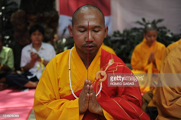 A Buddhist monk leads prayers at the launching of threeday ecumenical prayer and fasting against corruption near the presidential palace in Jakarta...