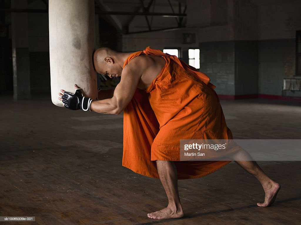 Buddhist monk leaning head on punch bag, side view : Foto stock