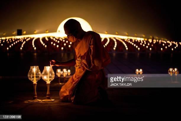 Buddhist monk lights candles during Makha Bucha celebrations at Wat Dhammakaya, north of Bangkok on February 26, 2021.