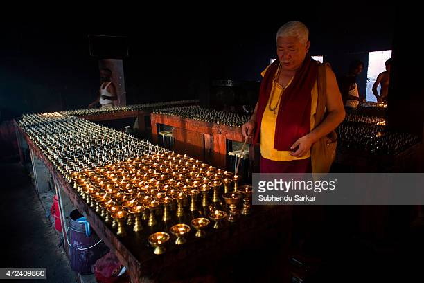 Buddhist monk lights up oil lamps at Mahabodhi temple complex as a part of Buddha Purnima celebrations at Bodh Gaya the place where lord Buddha...