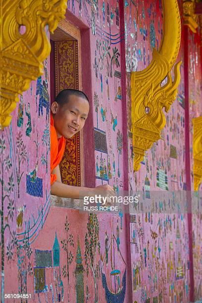 Buddhist monk looking out of Wat Xieng Thong window, Luang Prabang, Laos