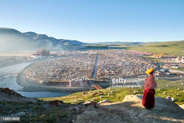 Buddhist monk looking out over valley shanty town, Baiyu, Sichuan, China