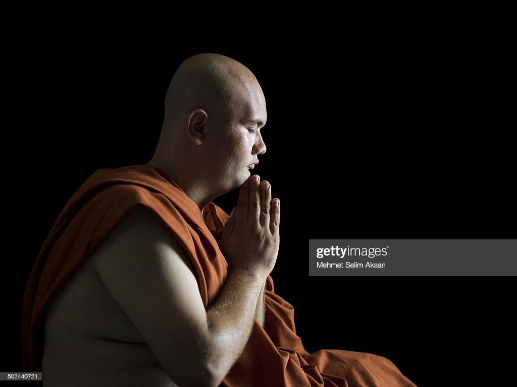 Buddhist Monk Meditating In Dark Stock Foto