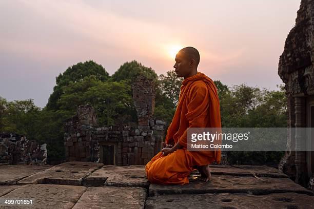 Buddhist monk meditating outside temple at sunset