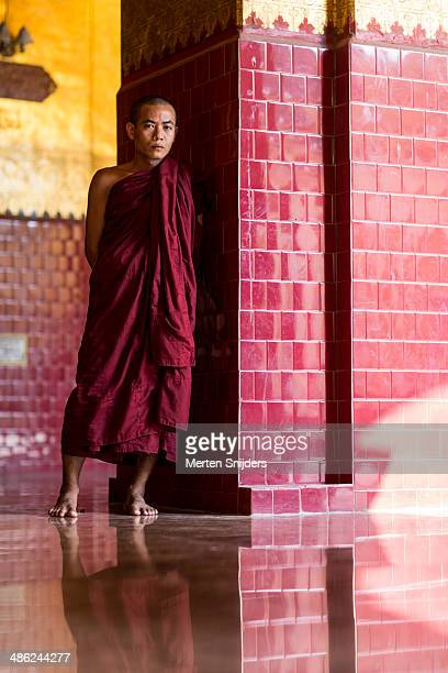 buddhist monk next to pillar in shade - merten snijders stock pictures, royalty-free photos & images