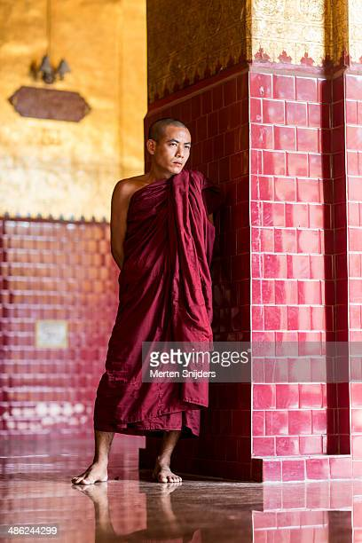 buddhist monk next to pillar in shade - merten snijders - fotografias e filmes do acervo