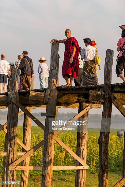 buddhist monk posing on u bein bridge - merten snijders - fotografias e filmes do acervo