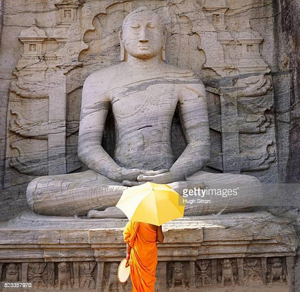 buddhist monk praying at the seated buddha at gal vihara in sri lanka - hugh sitton 個照片及圖片檔