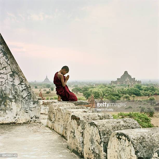 Buddhist monk praying on top of temple