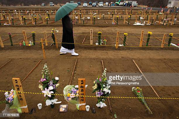 A buddhist monk prays for earthquake victims at a burial site one month after the earthquake and tsunami struck on April 11 2011 in Higashimatsushima...
