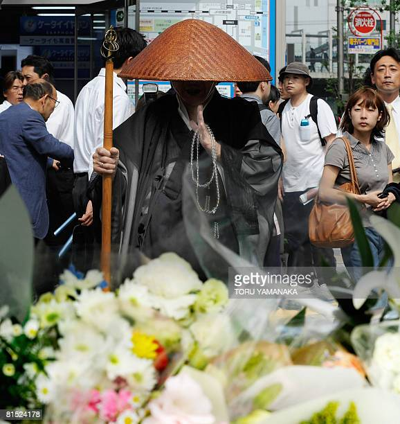 A Buddhist monk prays for victims before a makeshift altar at Tokyo's shopping and subculture town of Akihabara on June 11 three days after a man...
