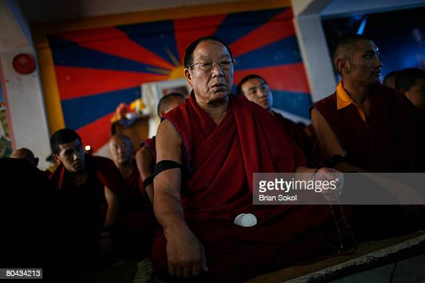 Buddhist monk prays in front of a Tibetan flag during a proTibet peace protest at a monastery March 30 2008 in Kathmandu Nepal According to reports...