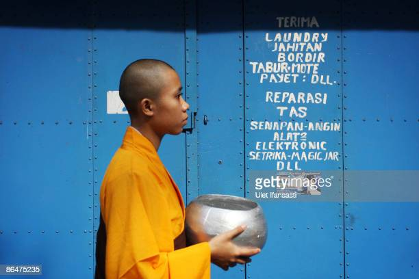 Buddhist monk prepares to receive a religious meal from Buddhist members of the public on Vesak Day commonly known as 'Buddha's birthday' at the...