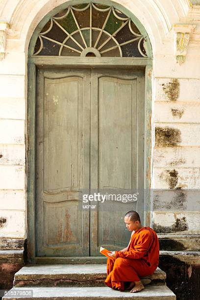 Buddhist  monk reading outside door