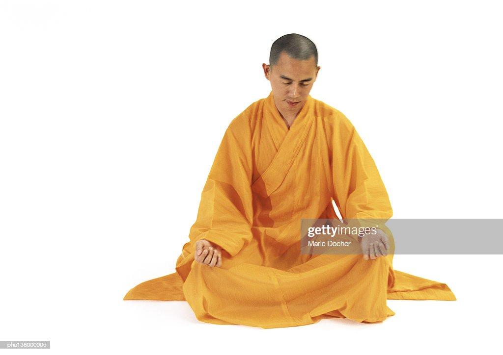 Buddhist monk sitting in lotus position, full length, blurred. : Stockfoto