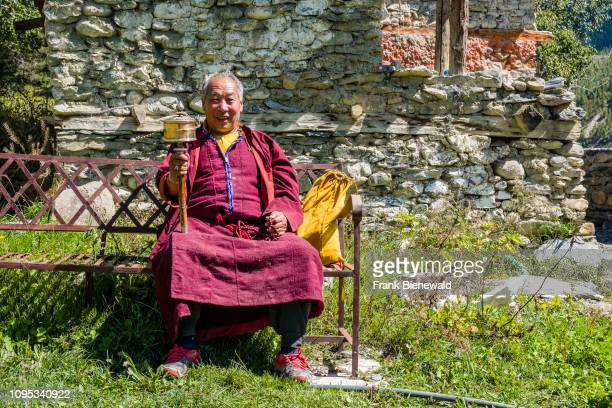 A buddhist monk sitting on a bench in front of a house turning a Prayer Wheel