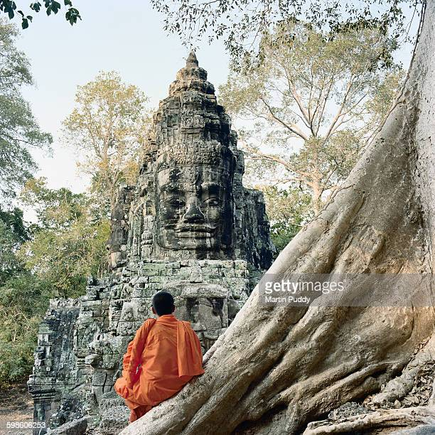 Buddhist monk sitting on tree roots at Angkor Wat