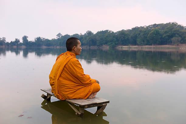 Buddhist monk sitting on water's edge