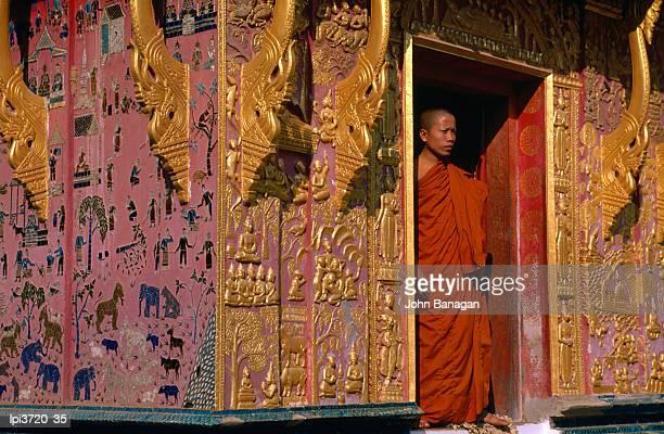 Buddhist monk standing in doorway of Wat Xieng Thong, Side view, Luang Prabang, Laos