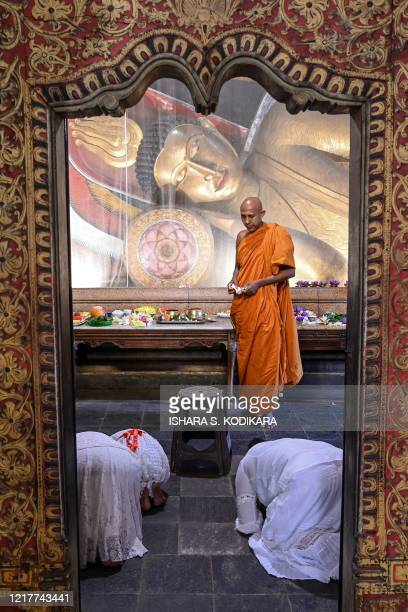 A Buddhist monk stands in front of devotees praying at the Kelaniya temple during the Poson Poya religious festival marking the arrival of Buddhism...