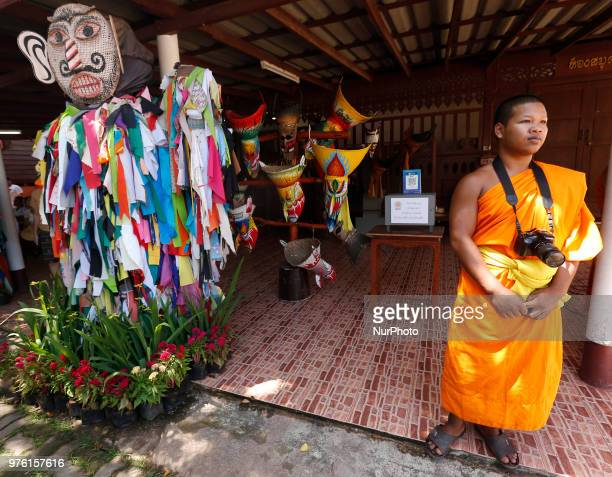 A Buddhist monk stands near a puppet is wear masks representing the spirits of the dead springing back to life during the annual Phi Ta Khon or Ghost...