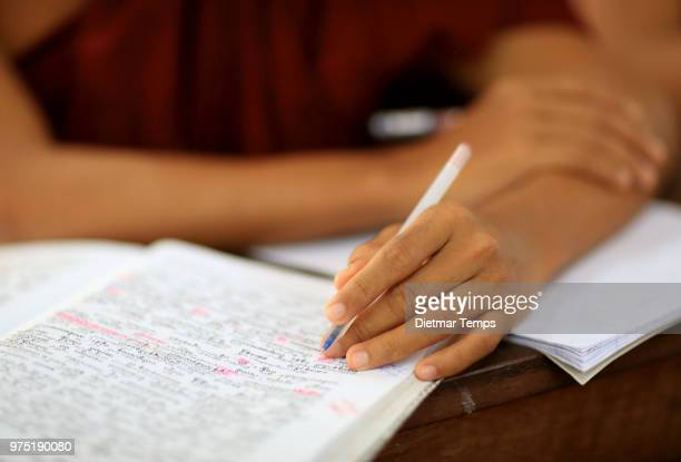 Buddhist monk studying Pali, close-up hand and textbook