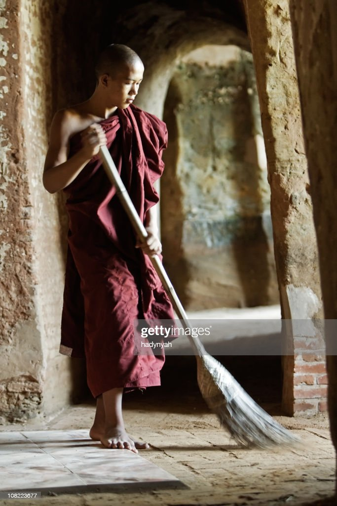 Buddhist monk sweeping temple : Stock Photo