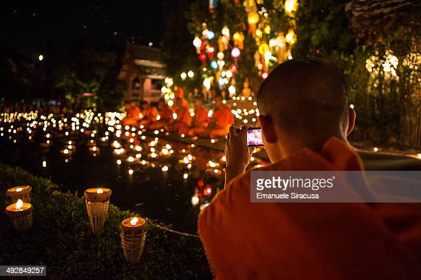 Buddhist monk takes a picture with his smartphone at Wat Pahn Tao, a Buddhist temple, in Chiang Mai, Thailand, during the Loi Krathong celebrations.