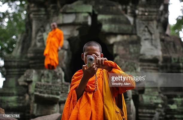 Buddhist monk takes photo with camera, Angkor Wat