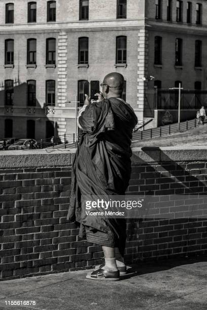 buddhist monk taking a picture with mobile phone - vicente méndez fotografías e imágenes de stock