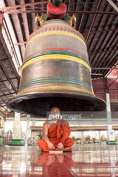 Buddhist monk that  reading a book under the bell