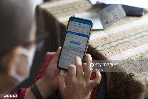 Buddhist monk uses the Aarogya Setu contact tracing application while registering for the Covishield Covid-19 vaccine, developed by...