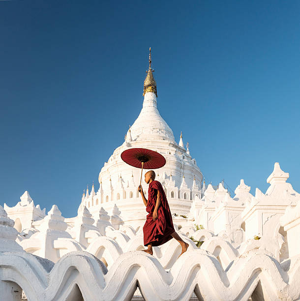 Buddhist monk walking across arches of temple