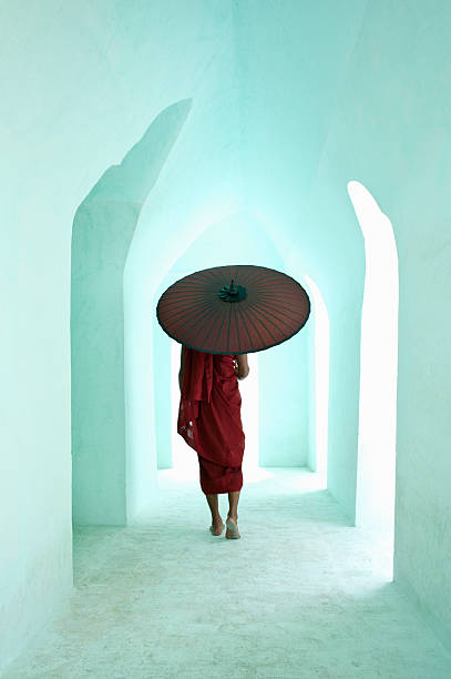 Buddhist monk walking along arched temple corridor