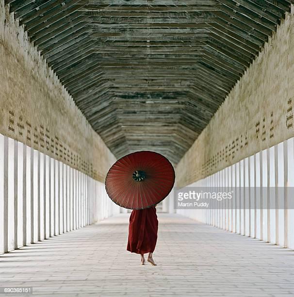 Buddhist monk walking along temple corridor