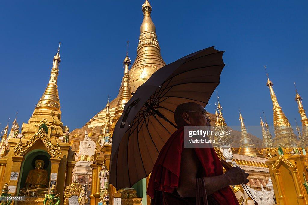 Buddhist monk and umbrella by the Shwedagon pagoda : News Photo