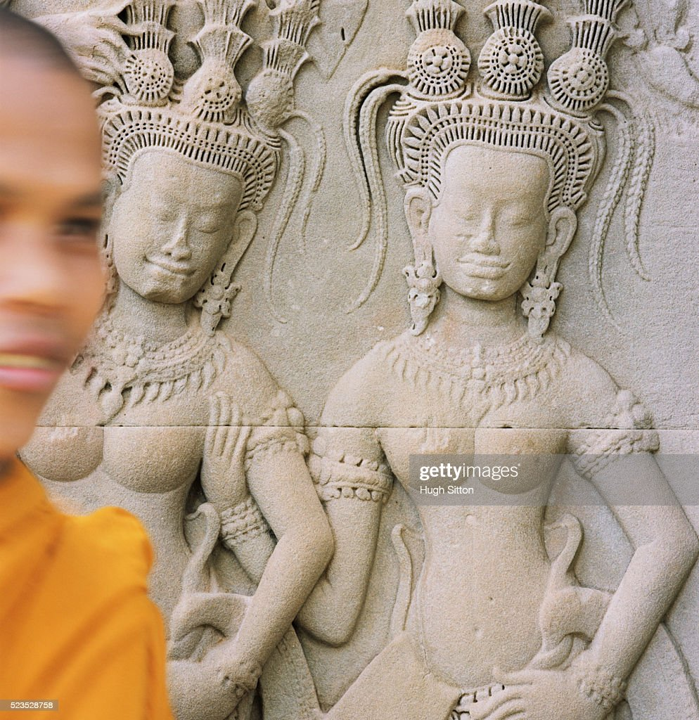 Buddhist Monk Walking by Relief Sculpture : Stock Photo
