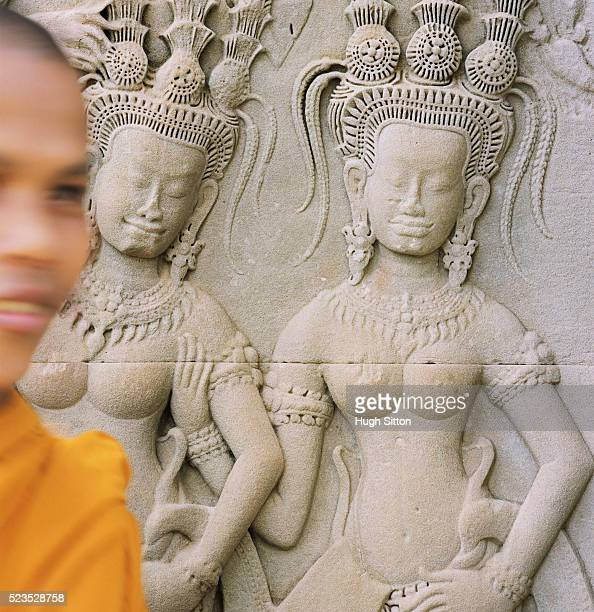 buddhist monk walking by relief sculpture - hugh sitton stock pictures, royalty-free photos & images