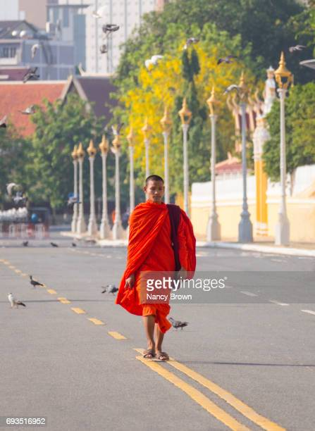 Buddhist Monk walking  onStreet by The Royal Palace in Phnom Penh Cambodia.