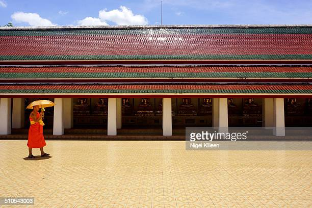 A Buddhist monk walks alone in front of Buddha statues and a Temple Building Wat Saket